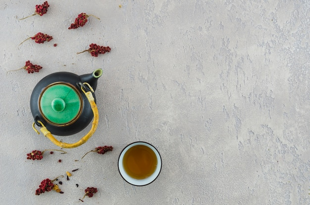 An elevated view of oriental teapot and herbal tea cup with herbs on texture backdrop Free Photo