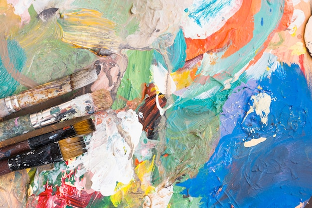 Elevated view of paint brushes over colorful messy background Free Photo