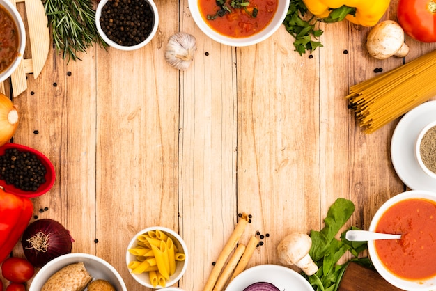 Elevated view of pasta ingredients arranged in frame on wooden surface Free Photo