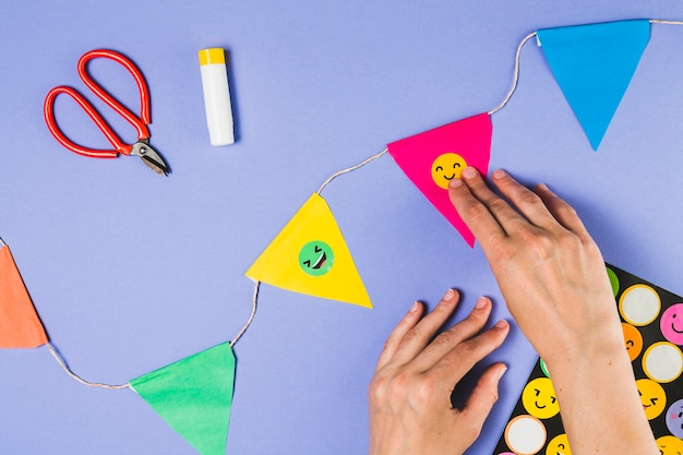 Elevated view of person hand sticking emoji sticker on bunting Free Photo