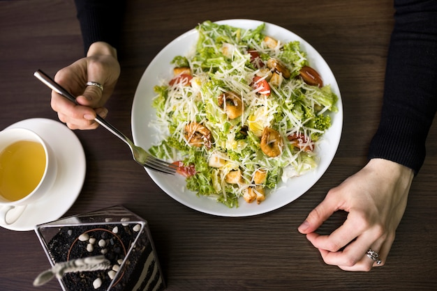 Elevated view of a person having caesar salad with shrimp on white plate over table Free Photo