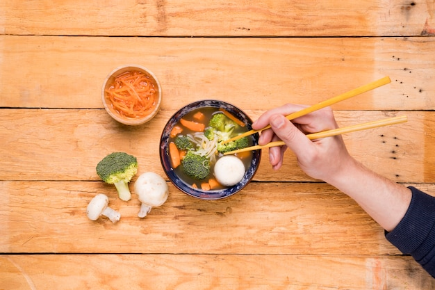An elevated view of a person's eating vegetables with chopsticks on wooden plank Free Photo