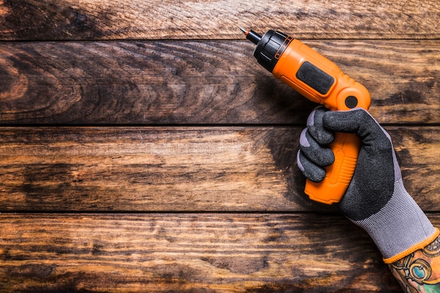 Elevated view of a person's hand holding cordless drill on wooden background Free Photo