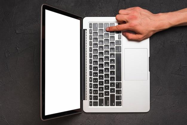 Vista elevata della mano di una persona usando il portatile su sfondo nero Foto Gratuite