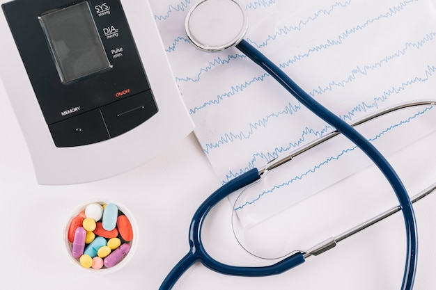 Elevated view of pills; cardiogram; stethoscope and blood pressure monitor Free Photo