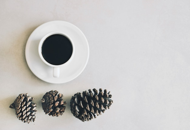 An elevated view of pine cones and coffee cup and saucer on white background Free Photo