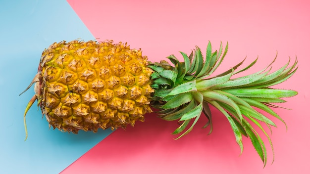 Elevated view of pineapple and blue cardboard paper on pink background Free Photo