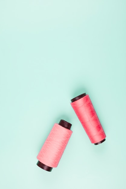 An elevated view of pink and coral spools on mint background Free Photo