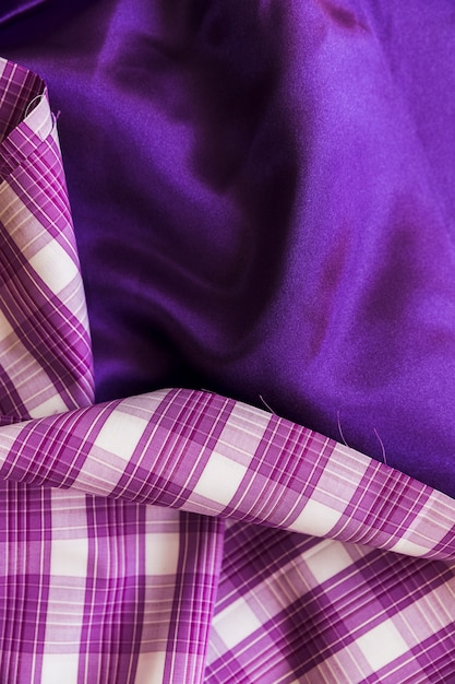 Elevated view of plaid textile on plain purple fabric material Free Photo