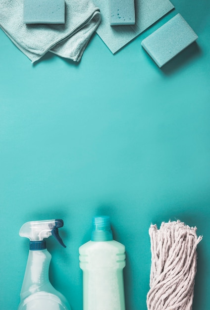 Elevated view of plastic bottles, mop head, sponge and napkin on turquoise backdrop Free Photo