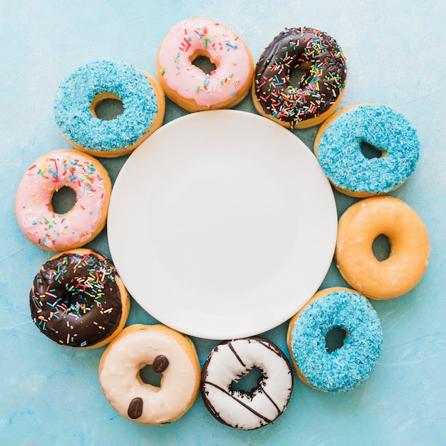 Elevated view of plate surrounded by various fresh donuts Free Photo