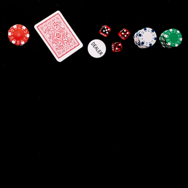 Elevated view of playing cards; dice; poker and dealer chips on black surface Free Photo