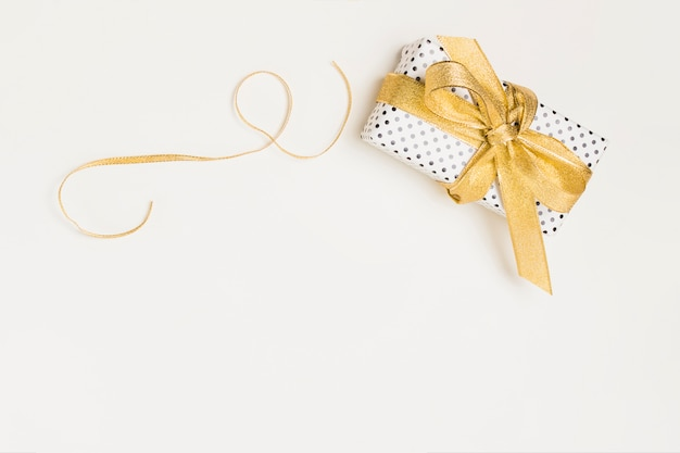 Elevated view of present box wrapped in polka dot design paper with shiny golden ribbon isolated on white backdrop Free Photo