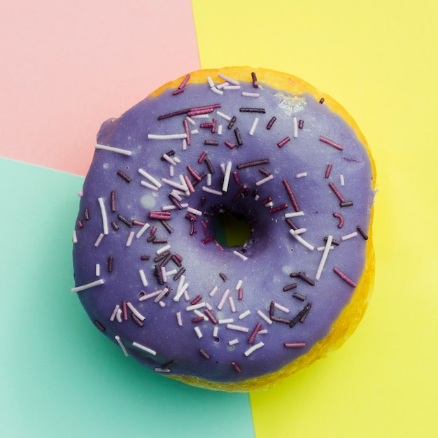 An elevated view of purple donut with sprinkles on colored