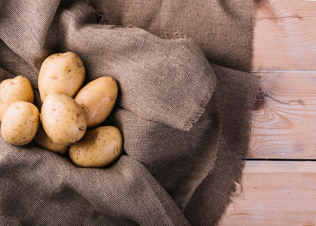 Elevated view of raw potatoes on sack cloth Free Photo