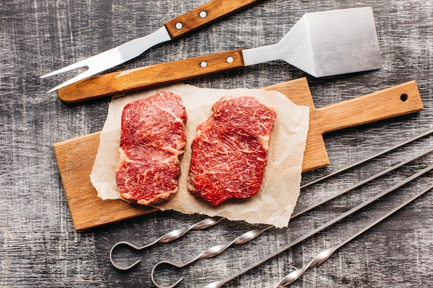 Elevated view of raw steak and barbecue utensil on wooden textured surface Free Photo