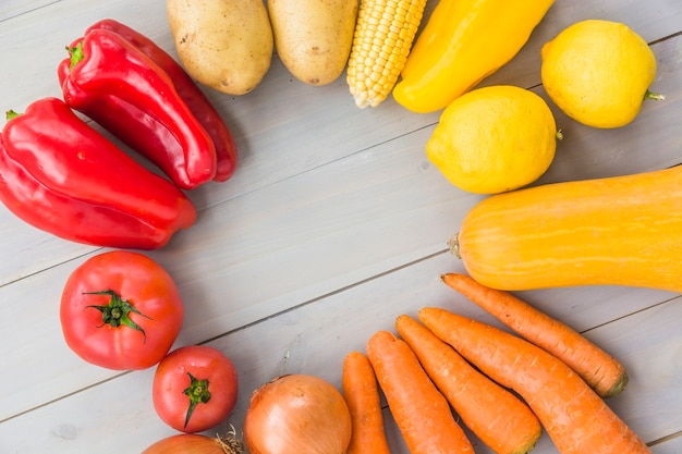 Elevated view of raw vegetables forming frame on wooden background Free Photo