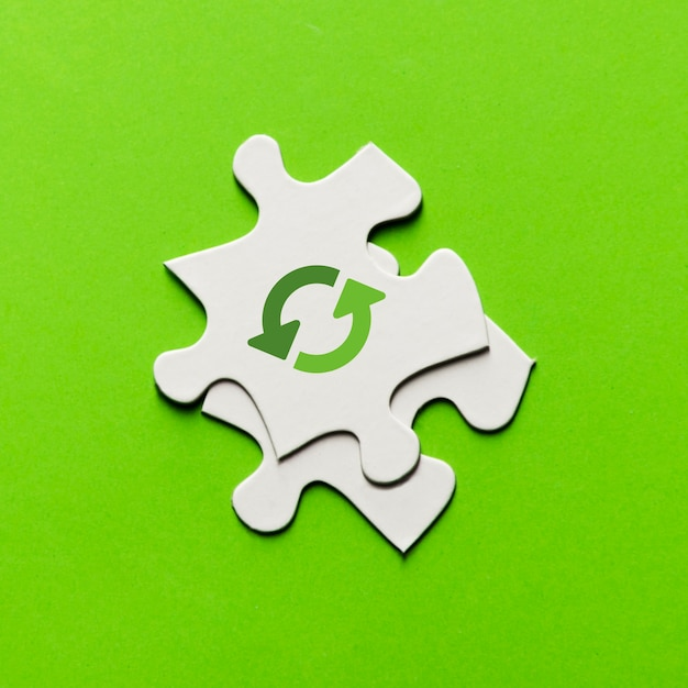 Elevated view of recycling icon on white puzzle piece over green backdrop Free Photo