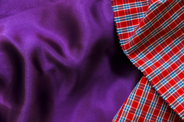 Elevated view of red chequered pattern and plain purple textile Free Photo