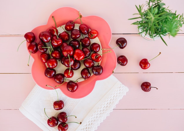 Elevated view of red cherries on flower shaped plate Free Photo