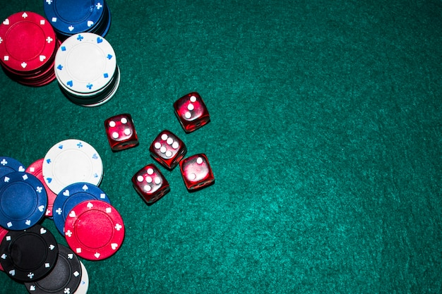 Elevated view of red dices and casino chips on green poker table Free Photo