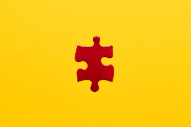 Elevated view of red jigsaw puzzle piece on yellow backdrop Free Photo