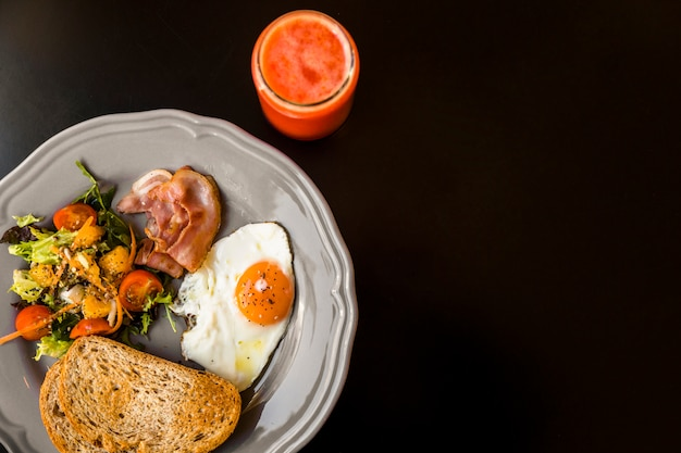 An elevated view of red smoothie in glass jar with toast; salad; bacon and fried egg on gray plate over black background Free Photo