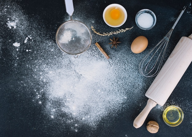 Elevated view of rolling pin; whisk; sieve; egg; walnut; oil and spice on kitchen counter Free Photo