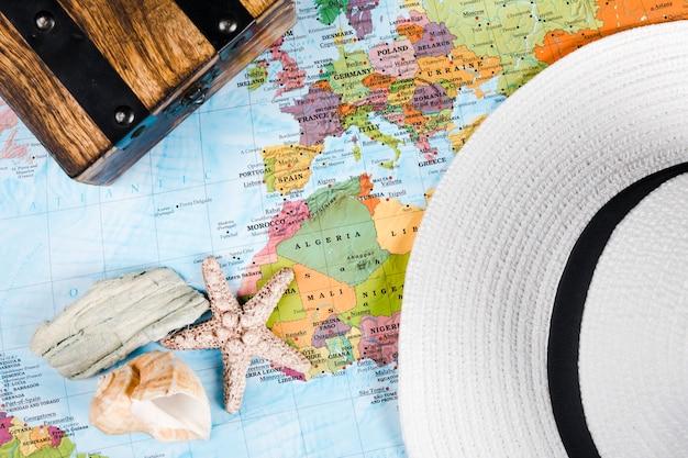 Vista elevata di conchiglie e cappello sulla mappa Foto Gratuite
