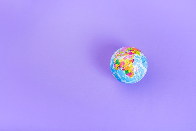 Elevated view of small plastic globe against purple backdrop Free Photo