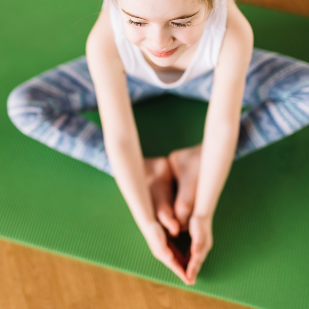 Elevated view of smiling little girl child doing yoga on green mat Free Photo