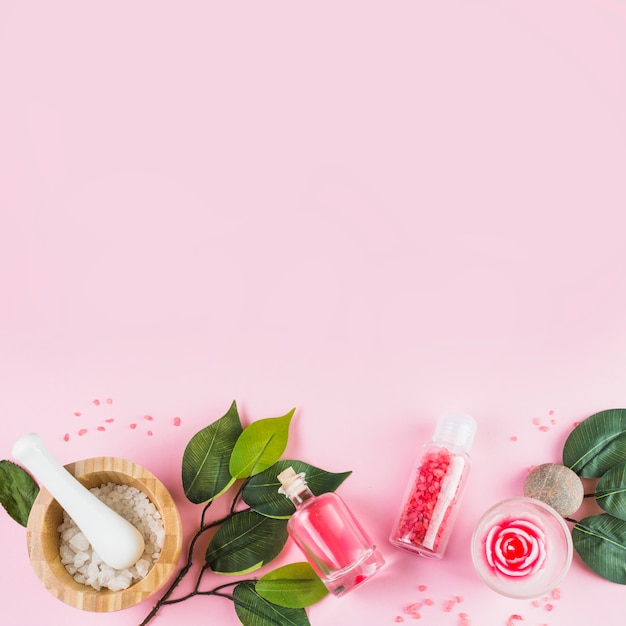 Elevated view of spa products and leaves at the bottom of pink surface Free Photo