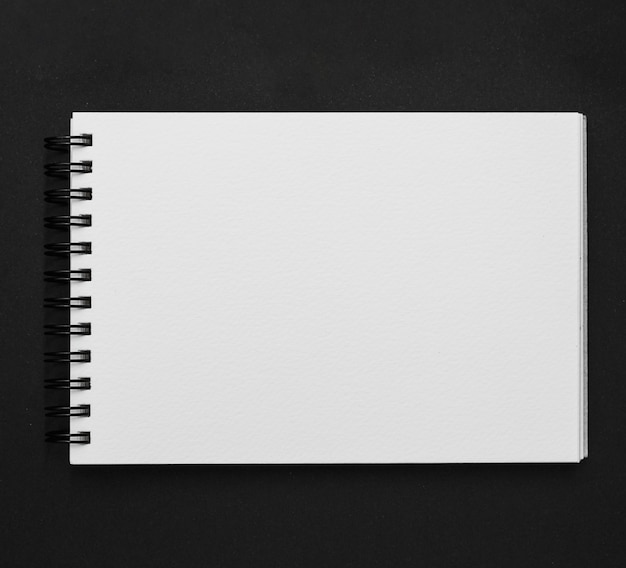 Elevated view of spiral notepad on black background Free Photo