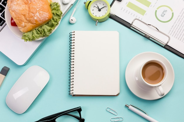 An elevated view of spiral notepad,breakfast,mouse and laptop on office desk Free Photo