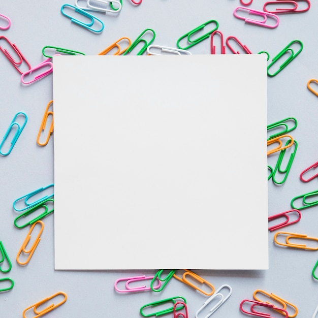 Elevated view of square shaped cardboard paper and many paper clips on grey background Free Photo