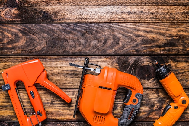 Elevated view of staple gun, electric jigsaw and driller on wooden background Free Photo