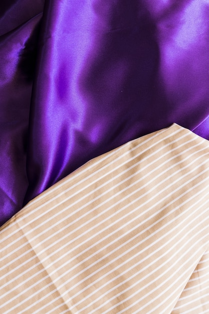 Elevated view of straight line pattern textile on silky purple drape Free Photo