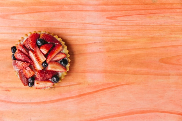 Elevated view of strawberry tart on wooden desk Free Photo