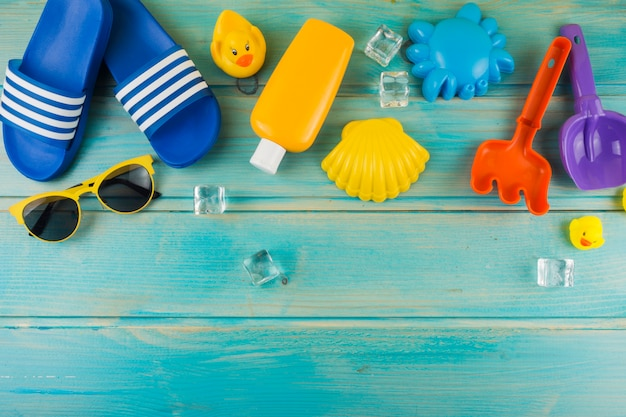 An elevated view of sunglasses; ice cubes; flip-flop; rubber duck; toys on turquoise wooden desk Free Photo