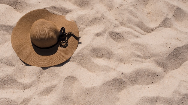 An elevated view of sunhat on beach sand Free Photo