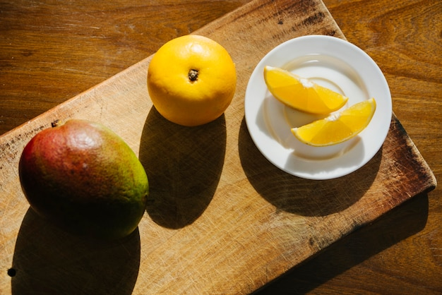 Elevated view of sweet lime and mango on chopping board Free Photo