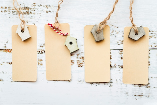 An elevated view of tags with miniature birdhouse on white desk Free Photo