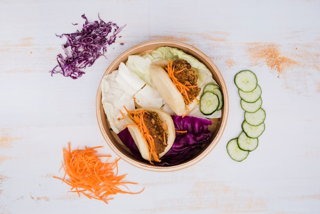 An elevated view of taiwan's traditional food gua bao in steamer with salad on wooden texture backdrop Free Photo