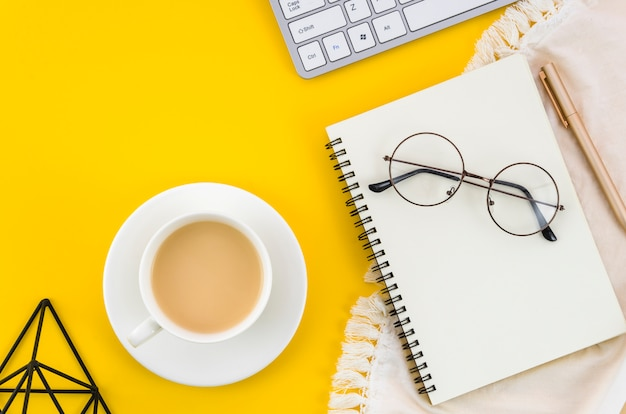 An elevated view of tea cup and saucer with eyeglasses; spiral notepad an eyeglasses on yellow backdrop Free Photo