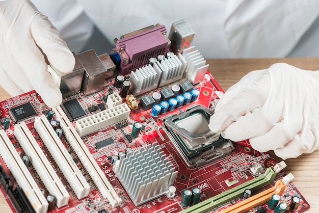 Elevated view of a technician working on computer motherboard Free Photo