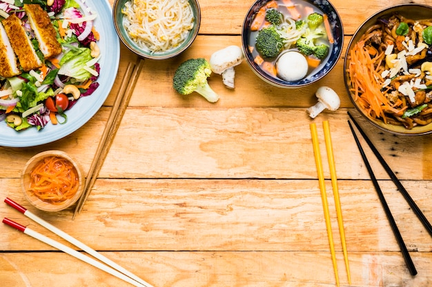 An elevated view of thai salad; sprouts; fish ball soup and noodles with different type of chopsticks on wooden table Free Photo