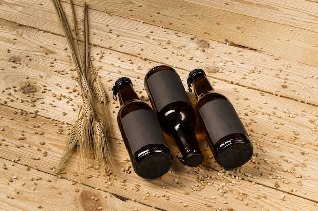 Elevated view of three beer bottles and ears of wheat on wooden backdrop Free Photo