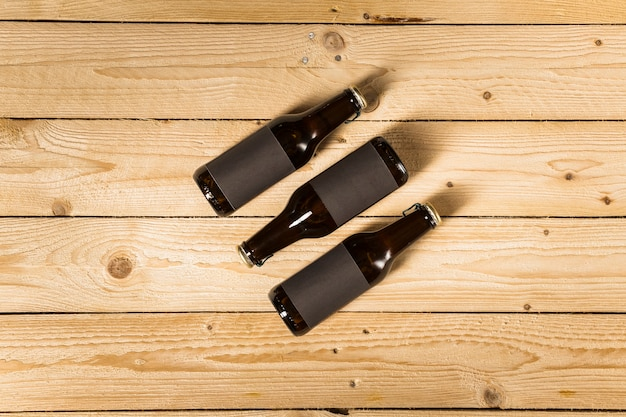 Elevated view of three beer bottles on wooden background Free Photo