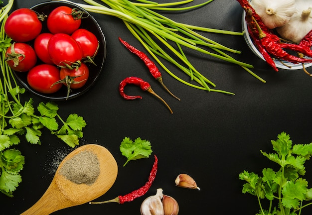 Elevated view of tomato; red chilies; spring onion; garlic; parsley and spices on black background Free Photo