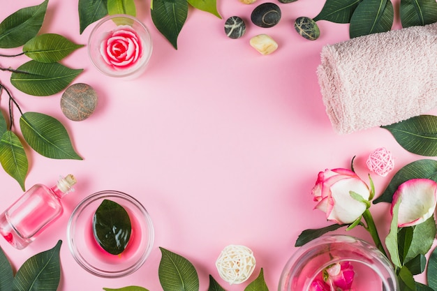 Elevated view of towels; spa stones; oil flower and leaves forming frame on pink surface Free Photo